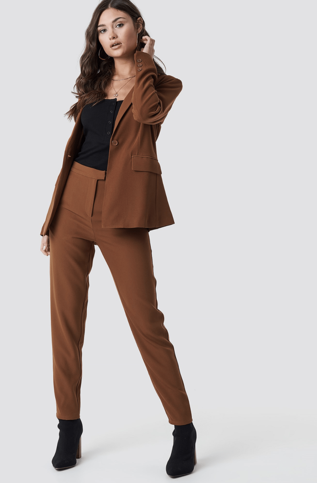 model wearing a brown suit, black top and booties