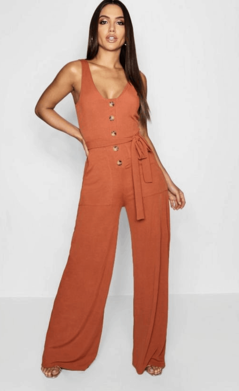 model in burnt-orange jumpsuit