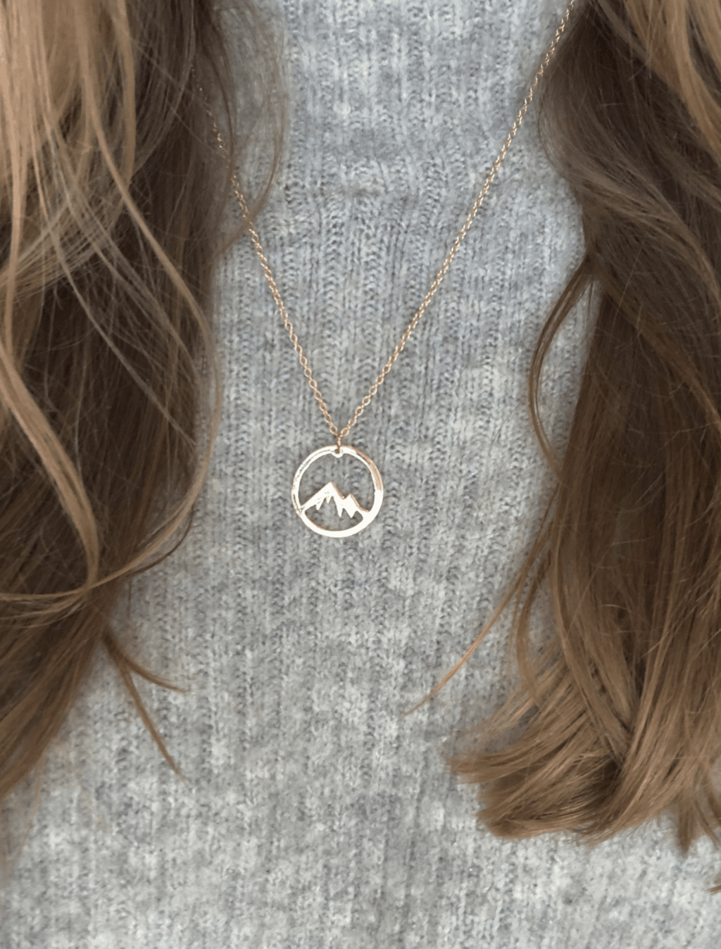 circle silver necklace with mountain shape inside