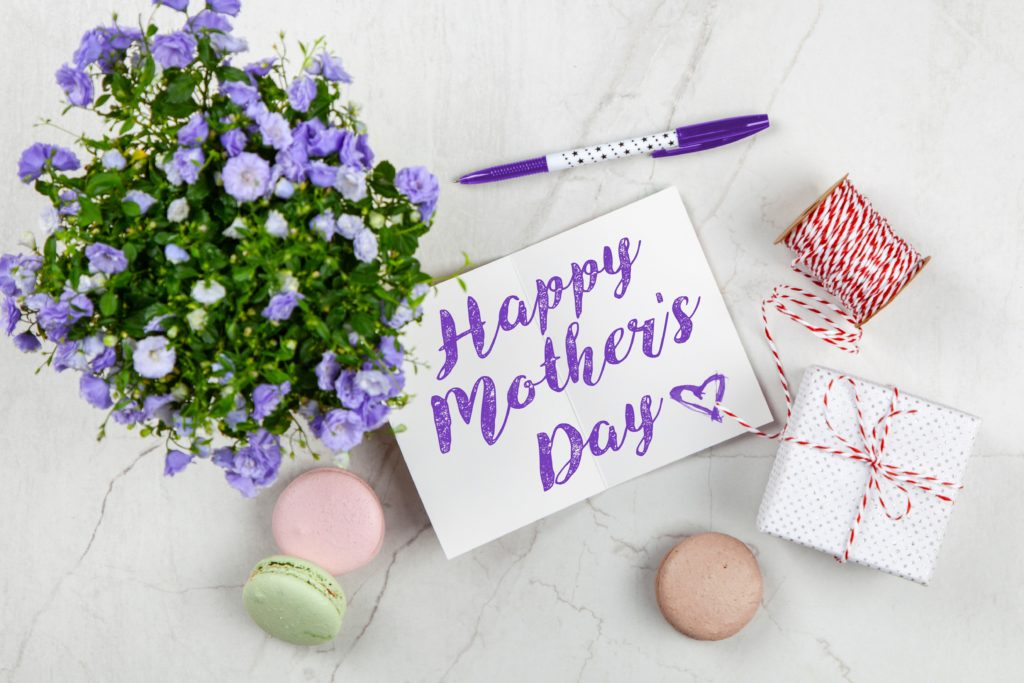 Mother's day gifts: Flat lay on a pale gray marble surface featuring purple flower plant, uncapped purple-and-white pen with a dotted design; white card that says