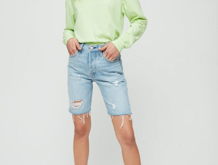 Woman wearing light neon green sweatshirt with light-wash denim Bermuda shorts and white sneakers