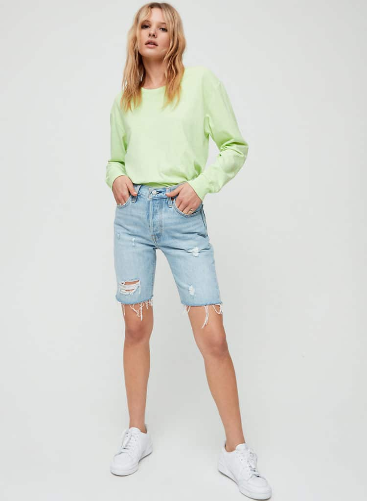 Woman with her hands partially in her pockets wearing a light neon green sweatshirt tucked into a pair of light-wash, distressed denim Bermuda shorts, white sneakers, and delicate gold rings on her little finger