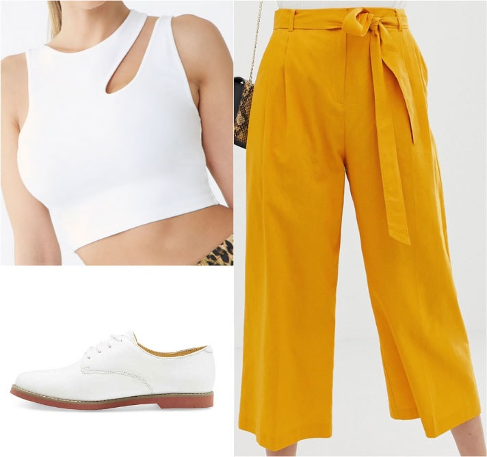 Gemma Chan outfit with mustard yellow trousers, white crop top, white oxfords