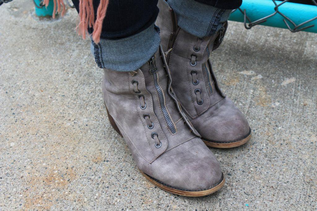 Brandi wears grey heeled booties with zippers.