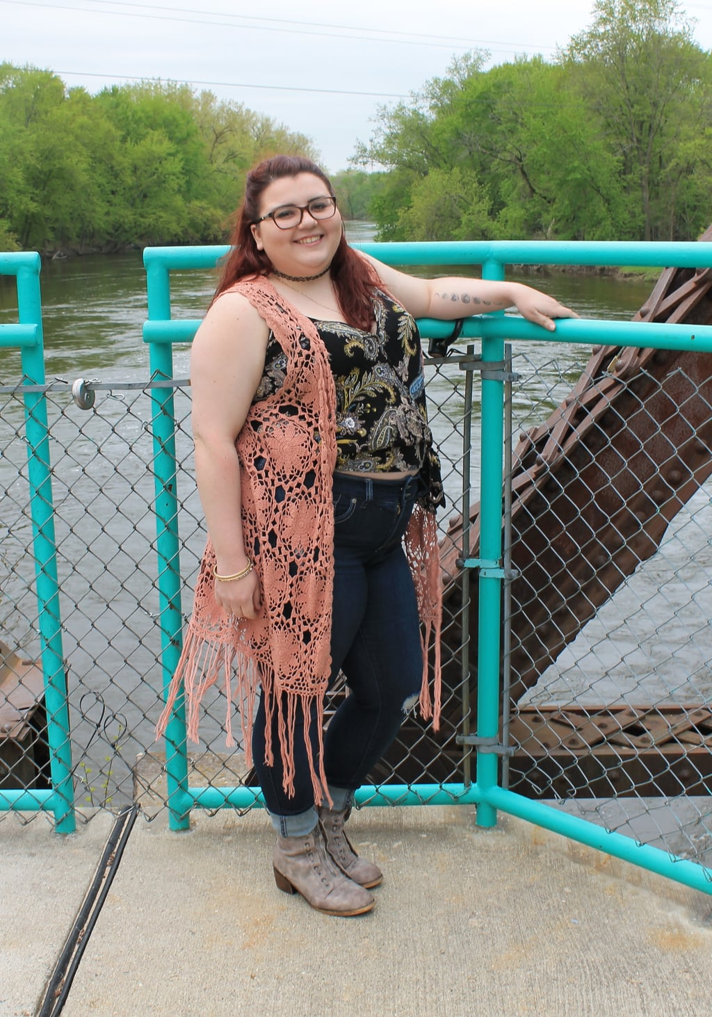 This Grand Valley State University student wears a coral crochet duster vest, a patterned black and gold wrap top, high-waisted skinny jeans, and grey booties.