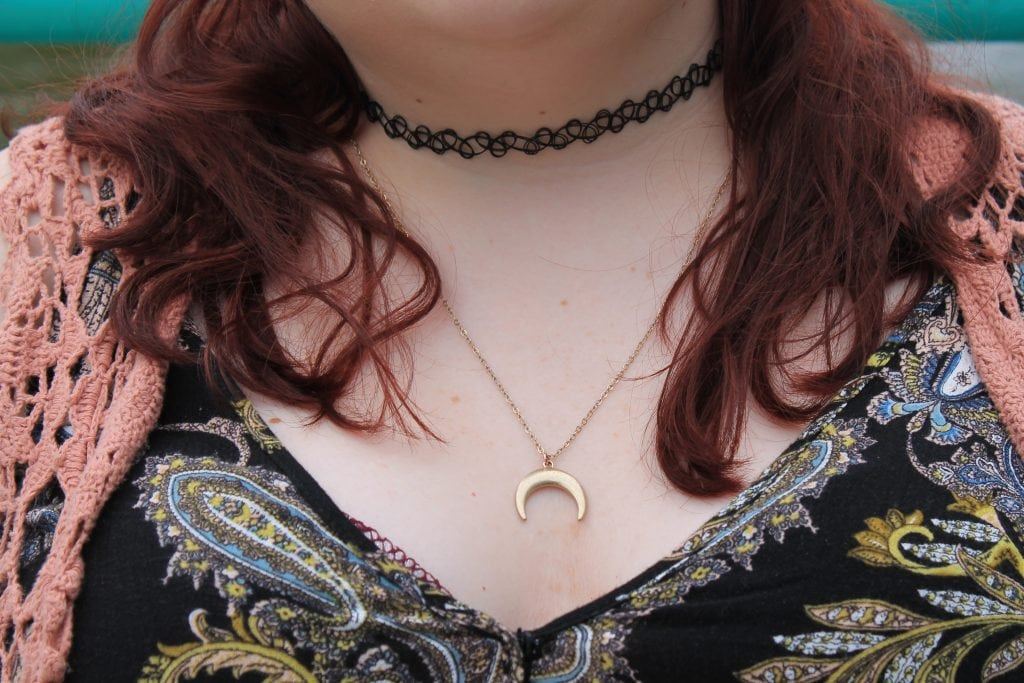 This student wears a black stretchy choker necklace and a simple gold moon pendant.
