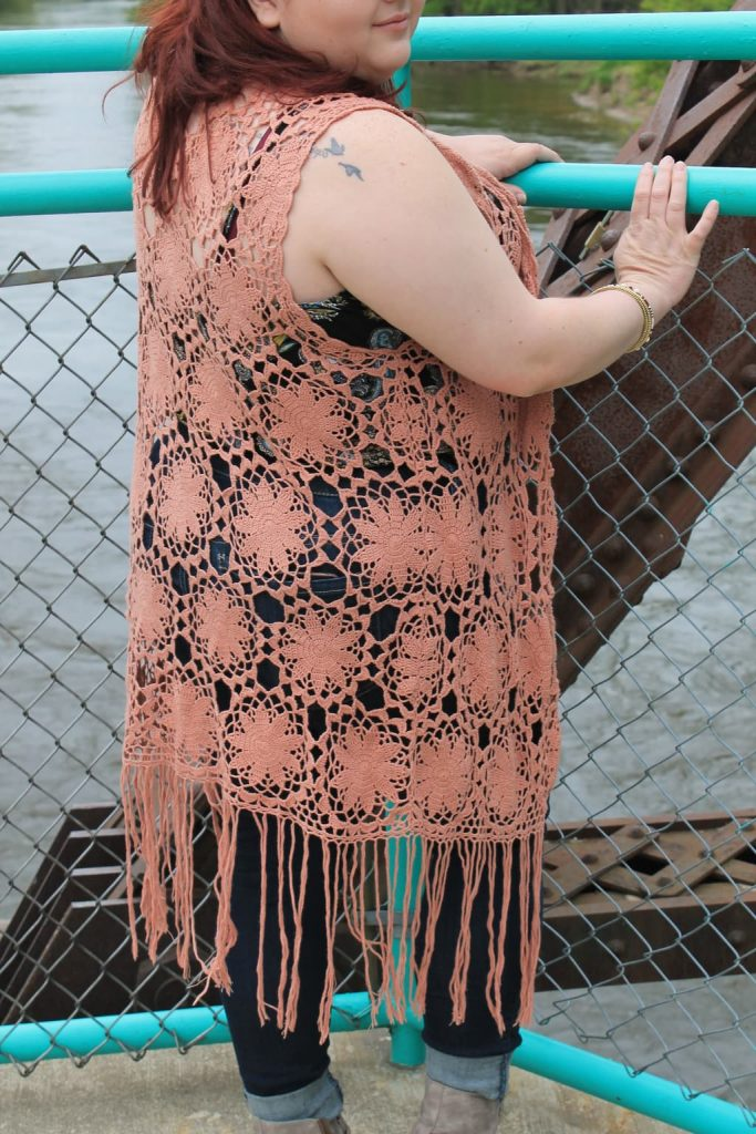 Brandi wears a long, coral, crochet duster vest with fringe at the bottom.