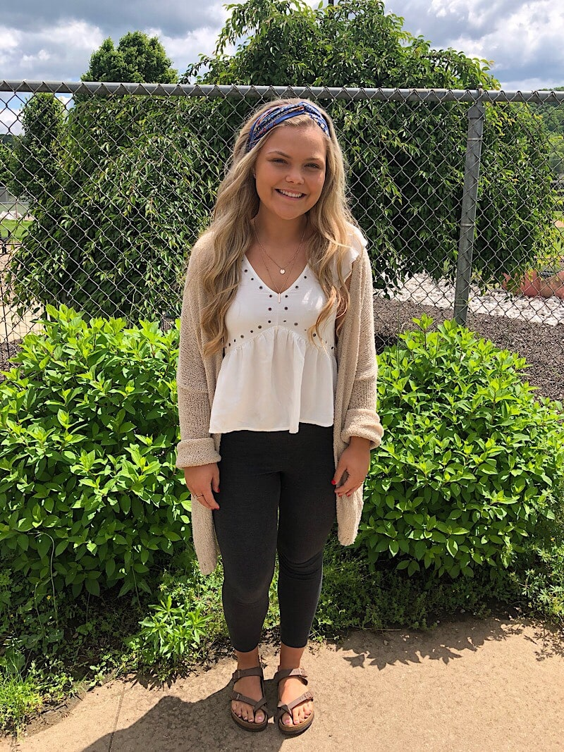 Kelsey wears a white ruffled top with rivet details, a long tan cardigan, black leggings, and brown birkenstock sandals.