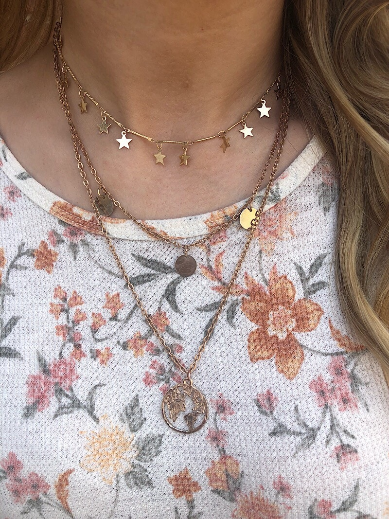 This WVU student wears layered gold pendant necklaces.