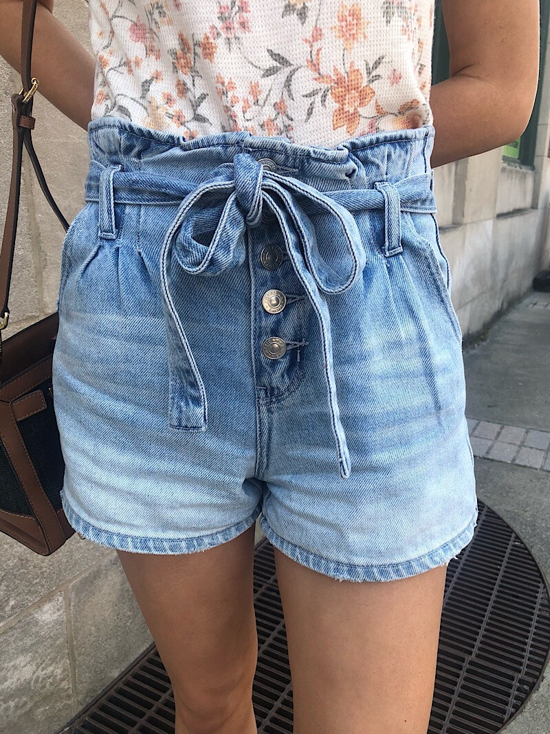 Savannah wears ombre-wash denim paper bag style shorts with a denim tied belt.