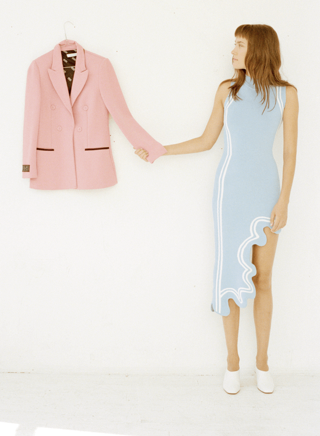 model in baby blue dress holding the sleeve of a pink blazer