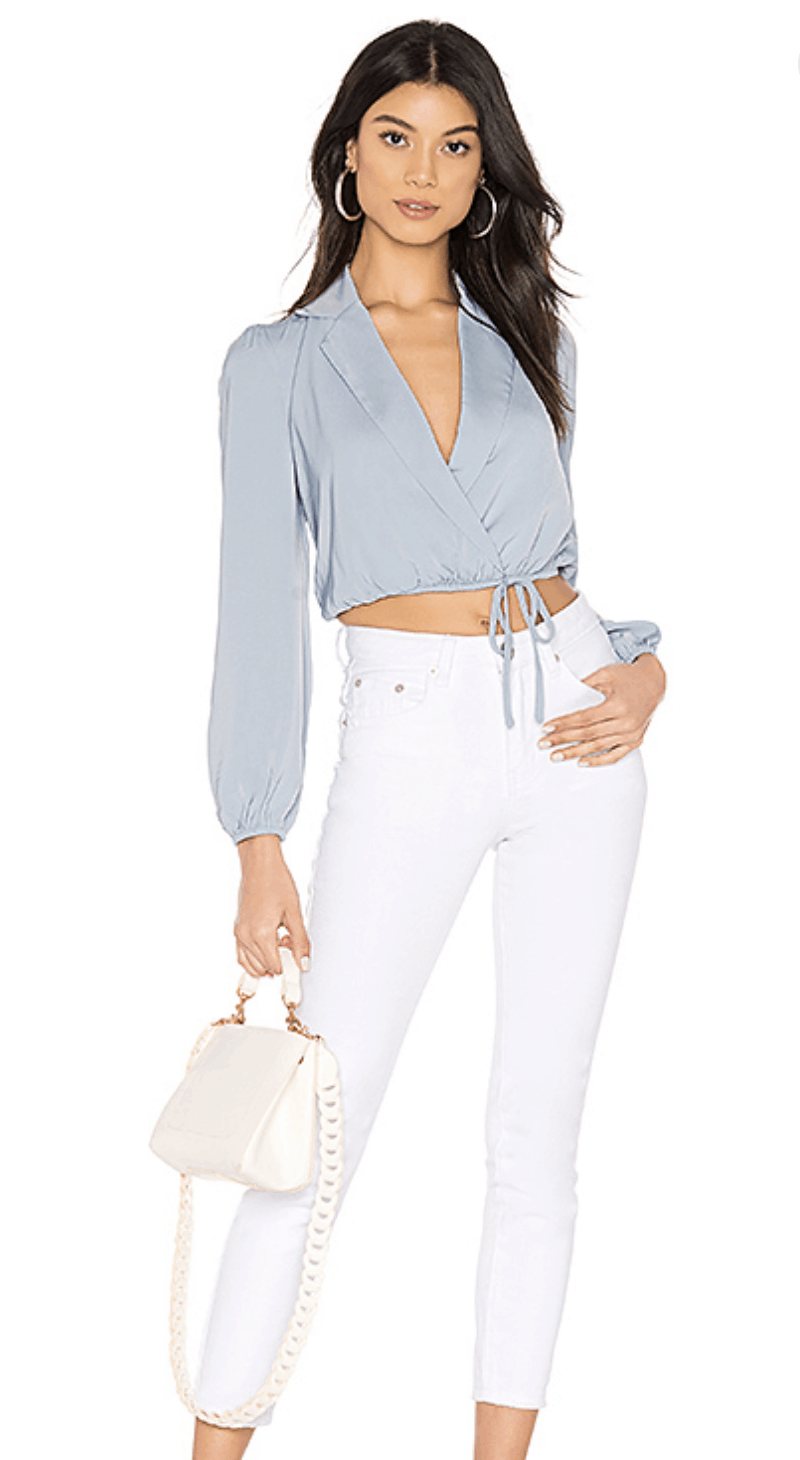 model in cropped collared baby blue top, white jeans, and white handbag