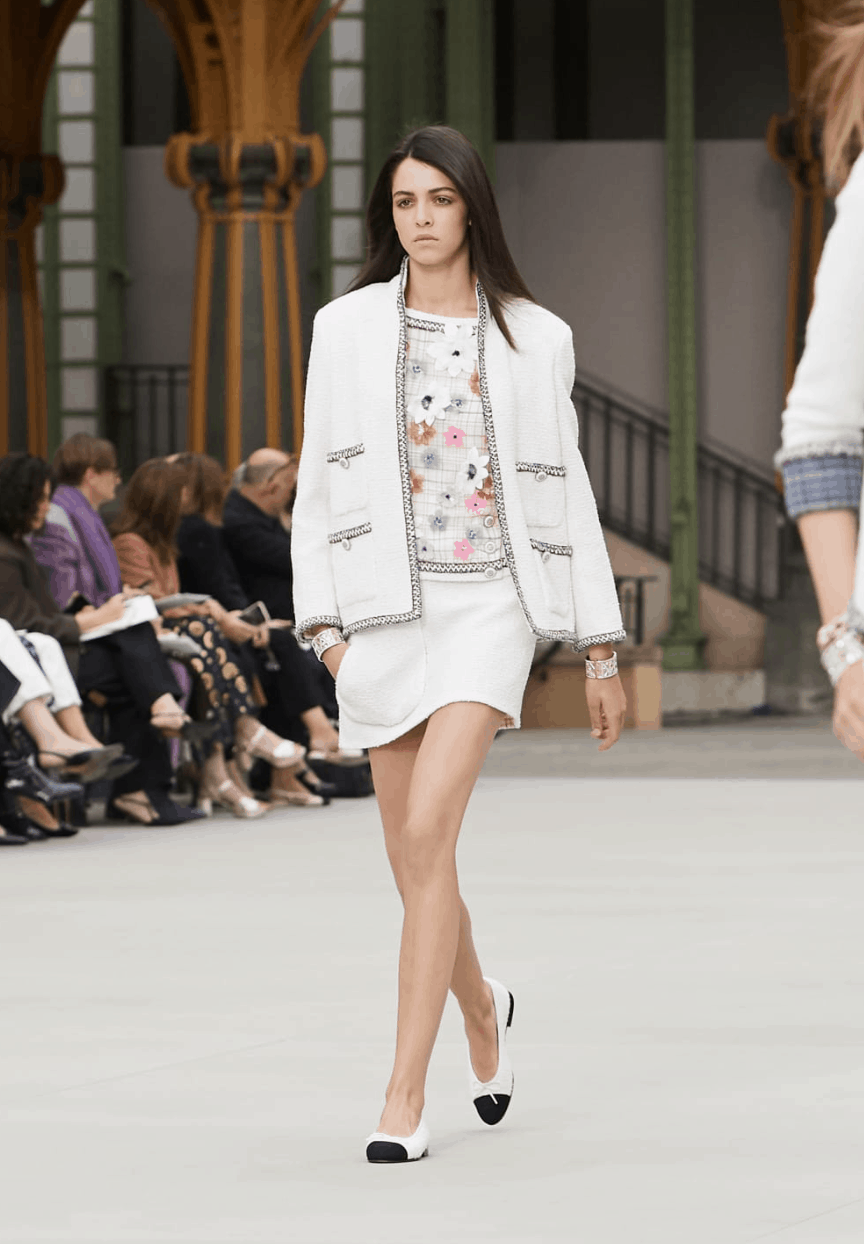 model in white skirt suit and blazer with floral top and flats