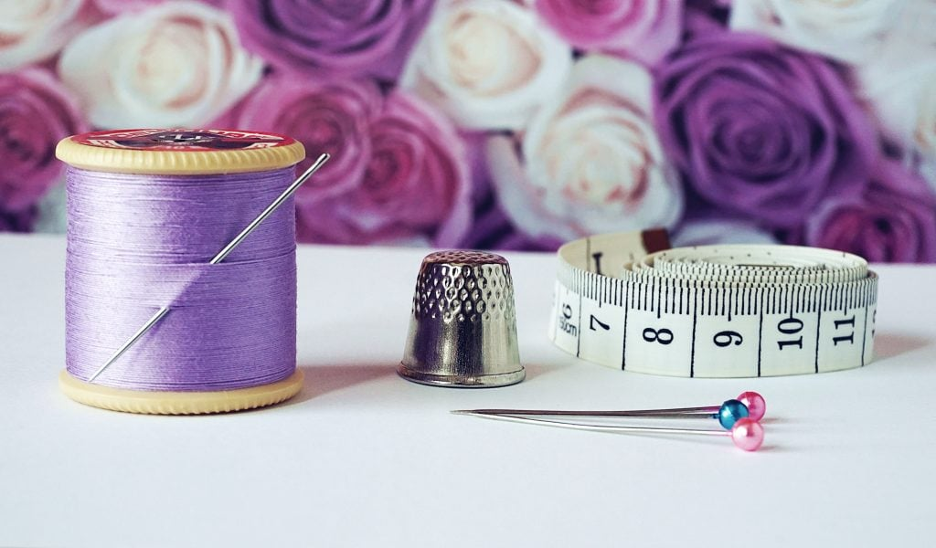 Bobbing of purple thread with needle, pins, and measuring tape