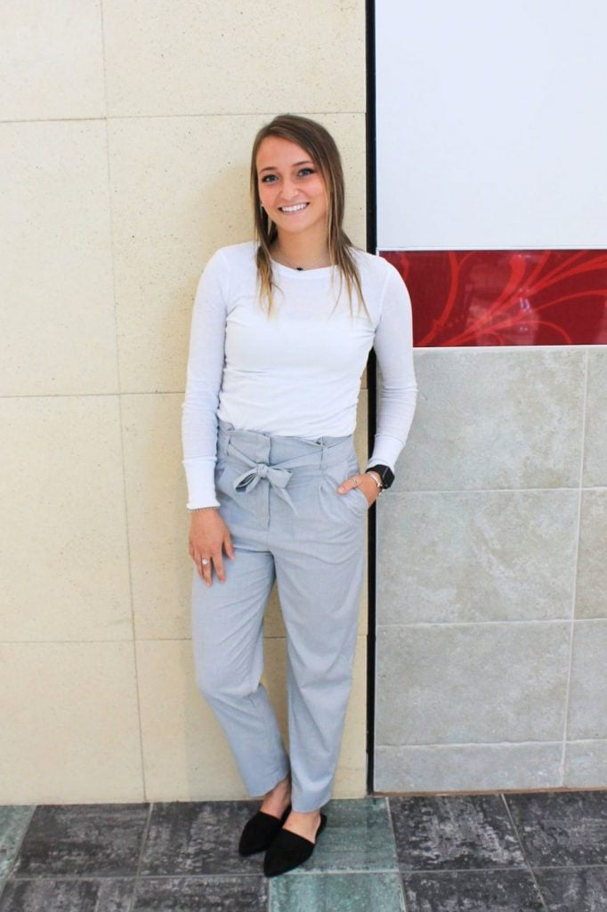 Darby, a student at Grand Valley State University, wears a white long sleeve shirt tucked into grey high-waisted taped leg trouser pants. She pairs it with black slides and stacked silver rings.
