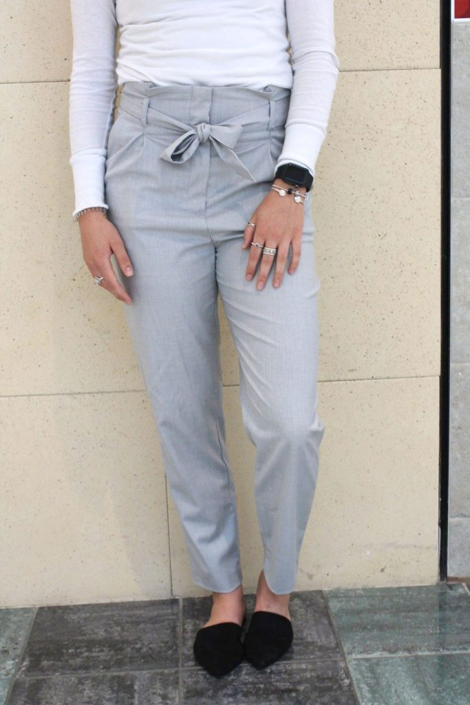 This Grand Valley State University student wears tapered grey trousers that have a tied fabric belt.