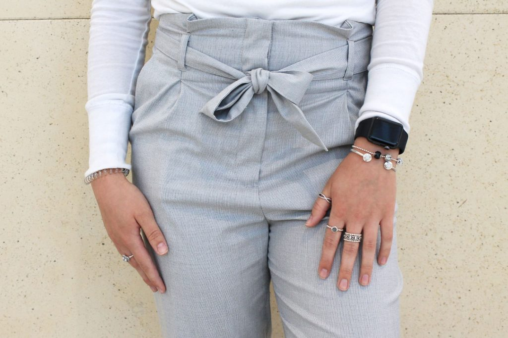 Darby wears stacked silver bracelets and rings.