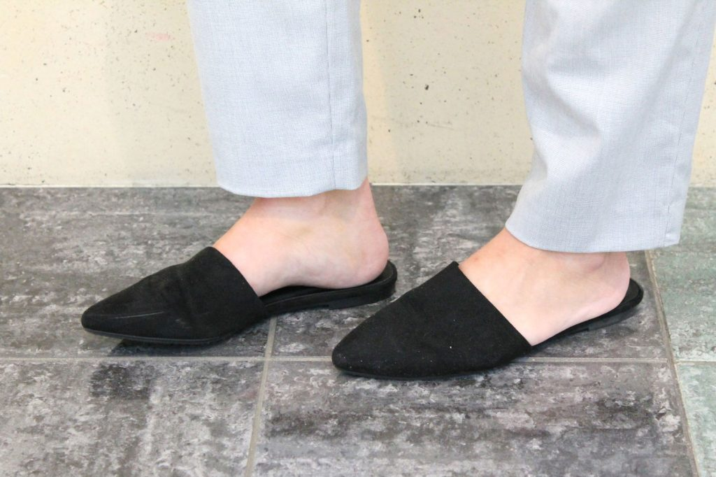 Darby wears flat black pointed-toe slide shoes.