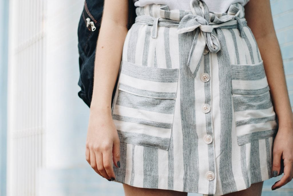 Close-up photo of girl wearing light blue-gray-and-white striped button-front mini skirt with tie-up paper bag waist.