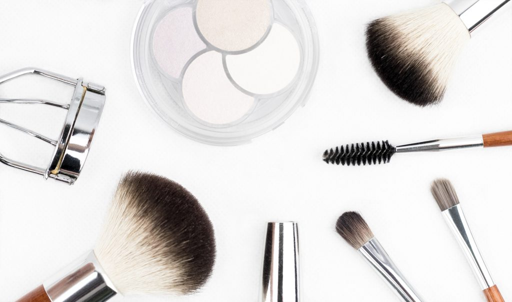 Makeup quiz - what makeup brand are you? Photo of makeup brushes and eyelash curler laid out on a table