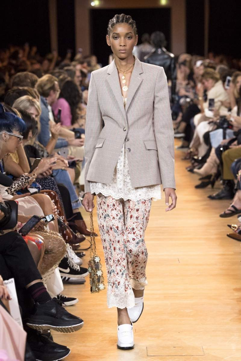 model in beige blazer, lacy top, and floral pants with white slip ons