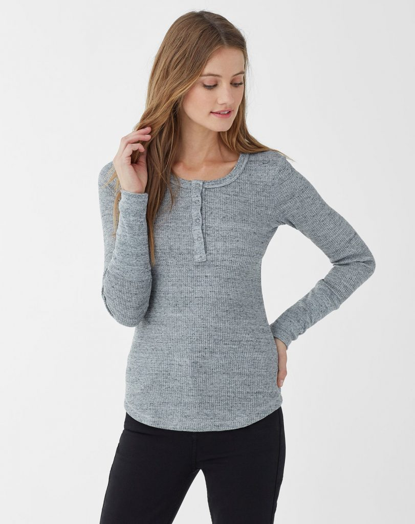 Woman wearing long-sleeved heather gray henley top with black pants.