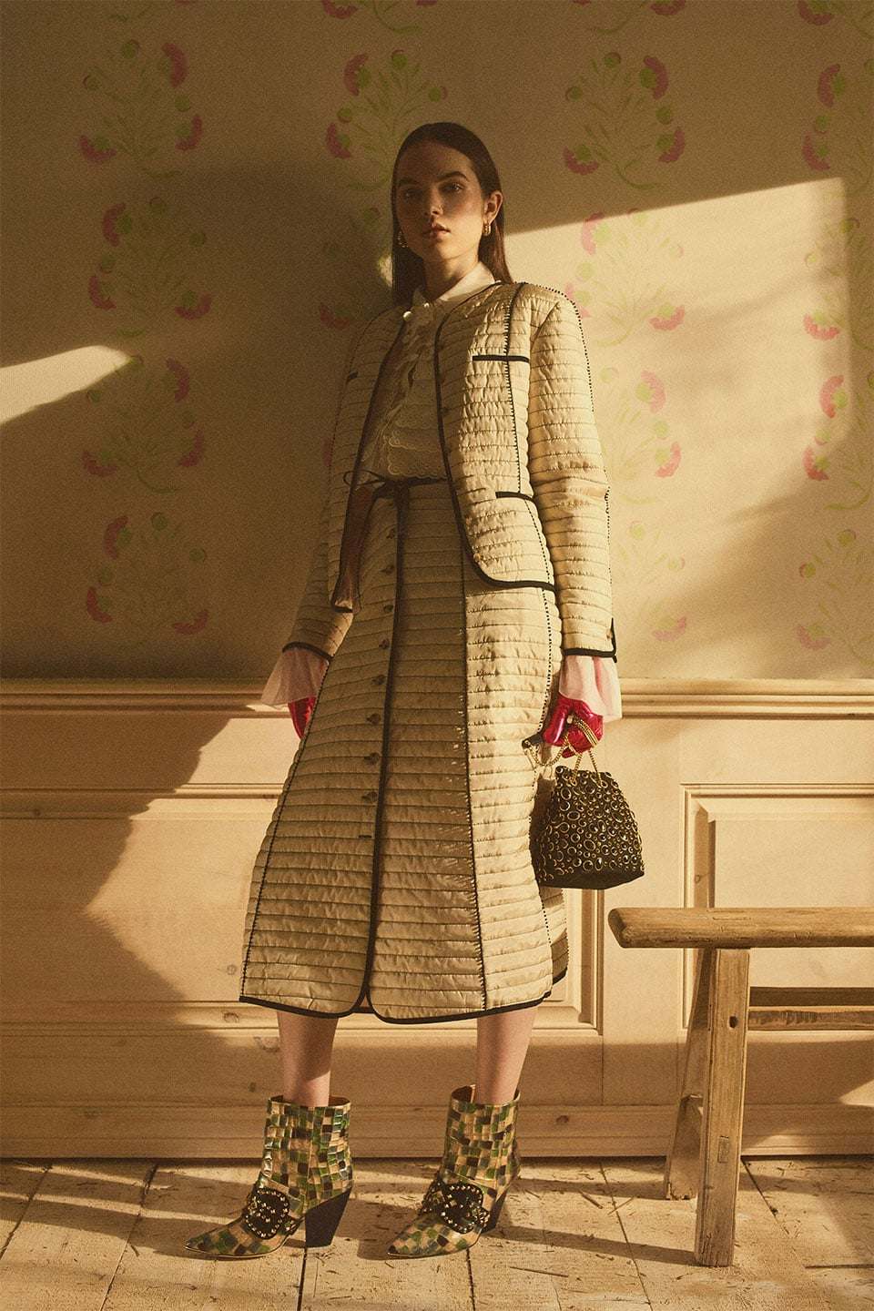 model in quilted suit jacket and midi skirt with white blouse, handbag, and booties.