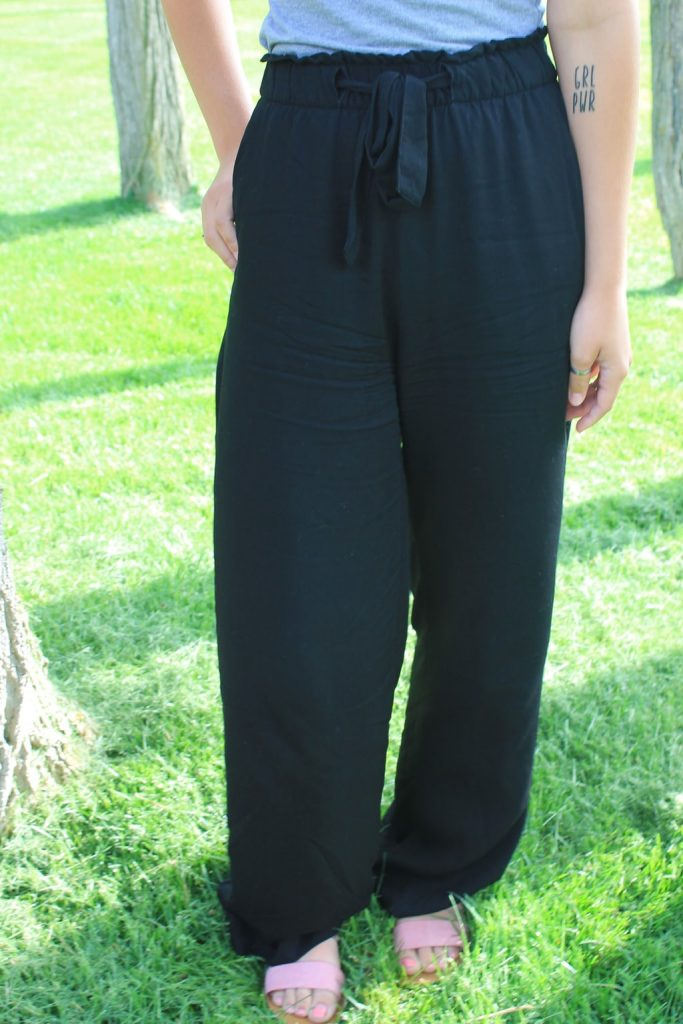 Emily wears flowy loose-fitted black pants with a tie at the waist.