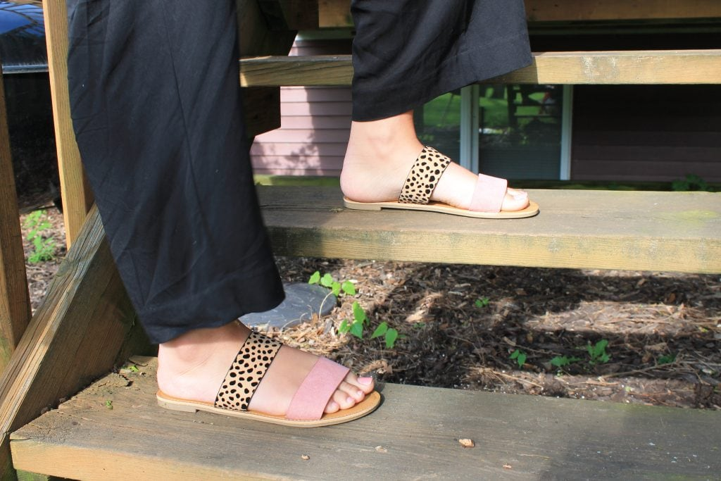 Emily wears flat pink and leopard slide sandals.