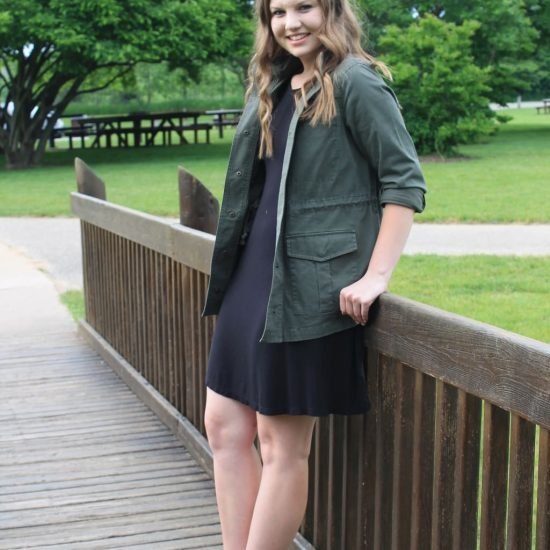 Rebecca wears an army green anorak jacket, a simple black shift dress, and brown criss-cross flat sandals.