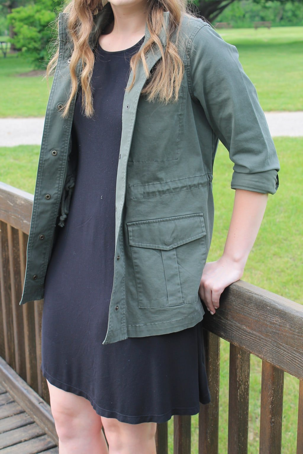 Rebecca wears a simple black shift dress with an army green anorak jacket.