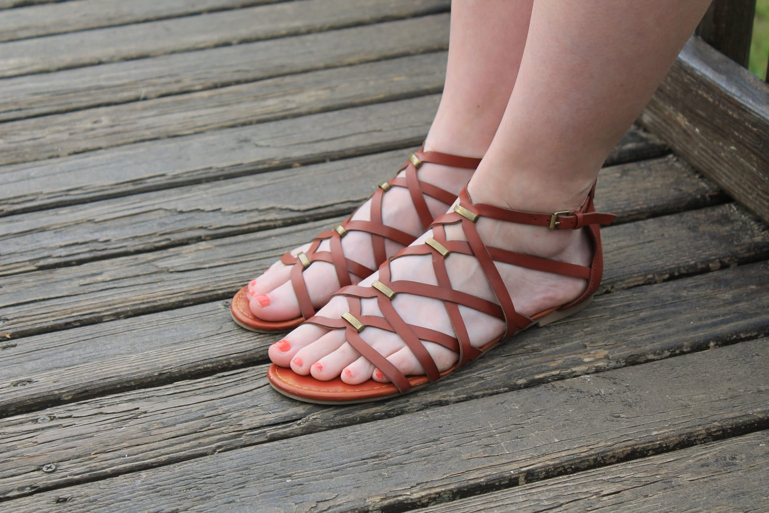 Rebecca wears flat brown sandals with gold details.