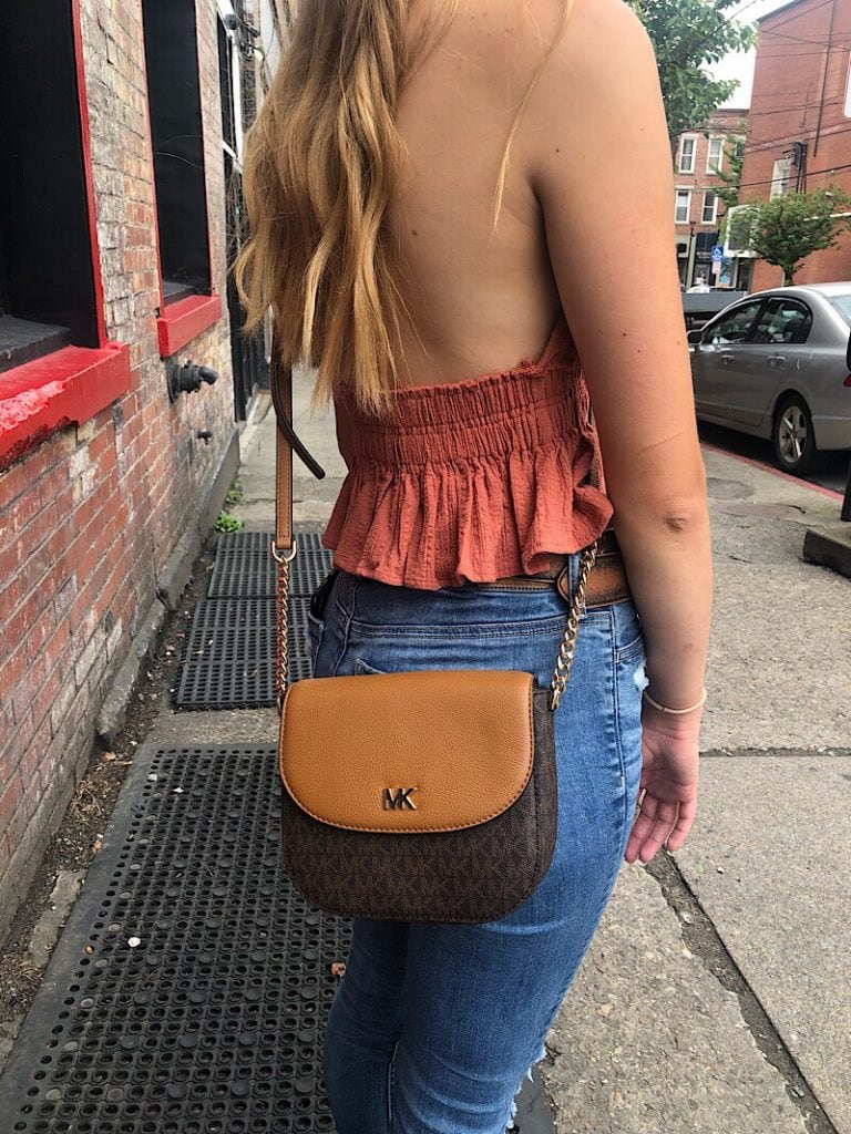 This West Virginia University student wears a tan and dark brown Michael Kors crossbody bag.