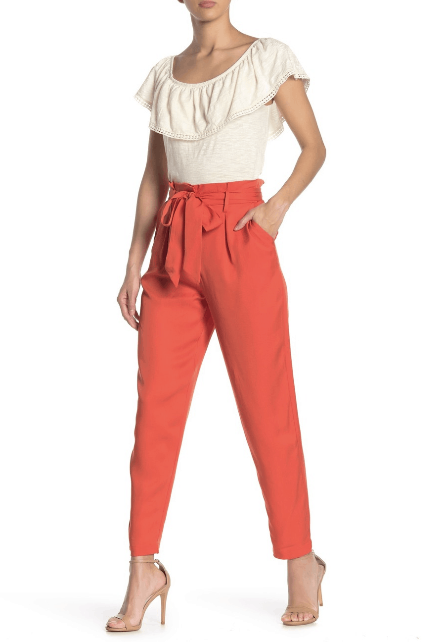 model in orange trousers, white top, and nude heels