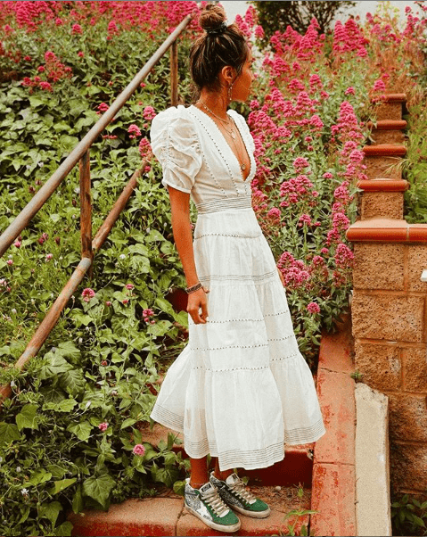 girl in longe white summer dress and green sneakers in front of a floral background