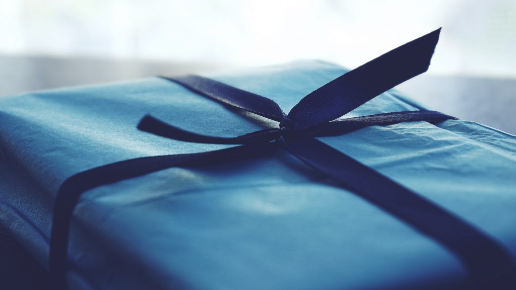Close-up photo of blue wrapped gift with navy blue ribbon