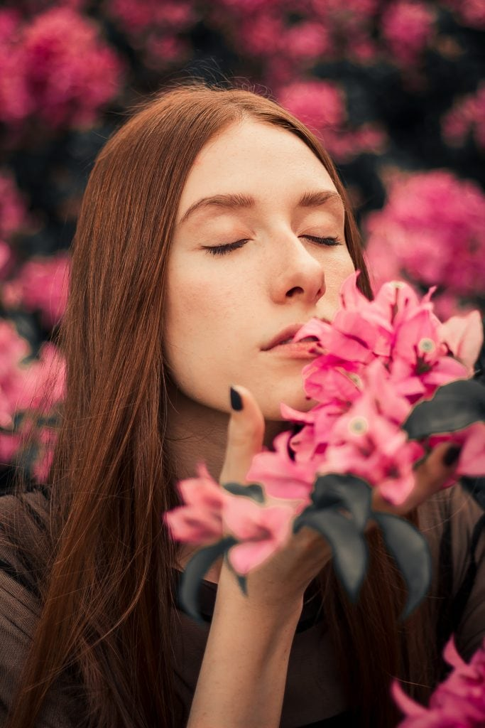 Close-up shot of woman with curly hair smelling pink flowers
