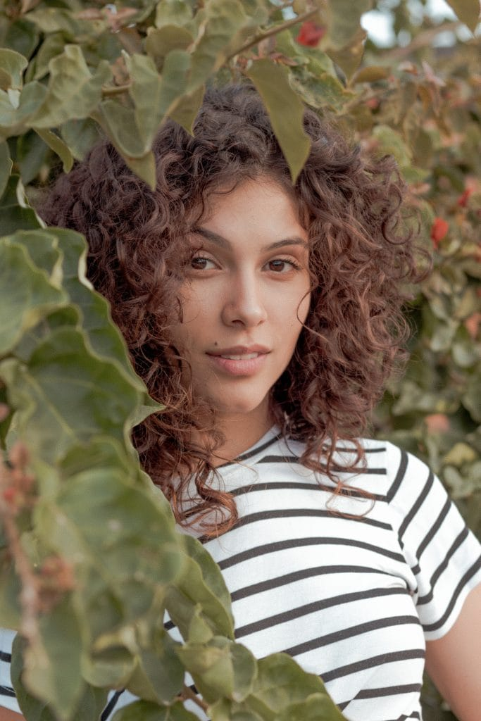 Close-up shot of woman with curly hair standing amongst leaves