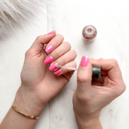 Girl painting glitter nail polish over bright pink nails