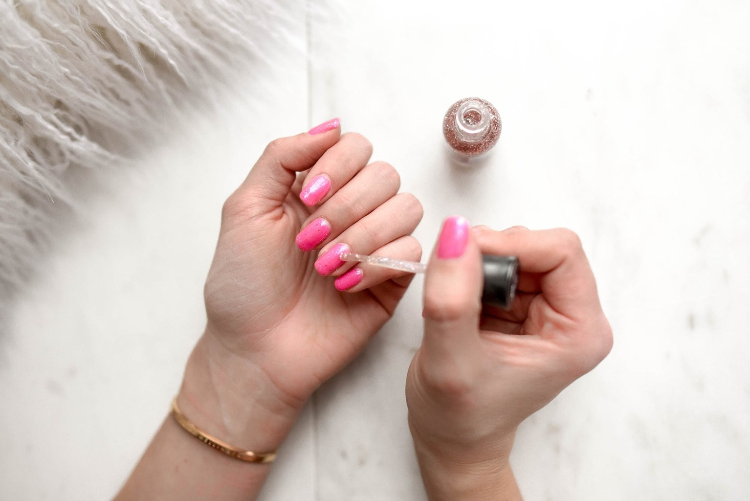 Girl painting glitter nail polish over bright pink nails