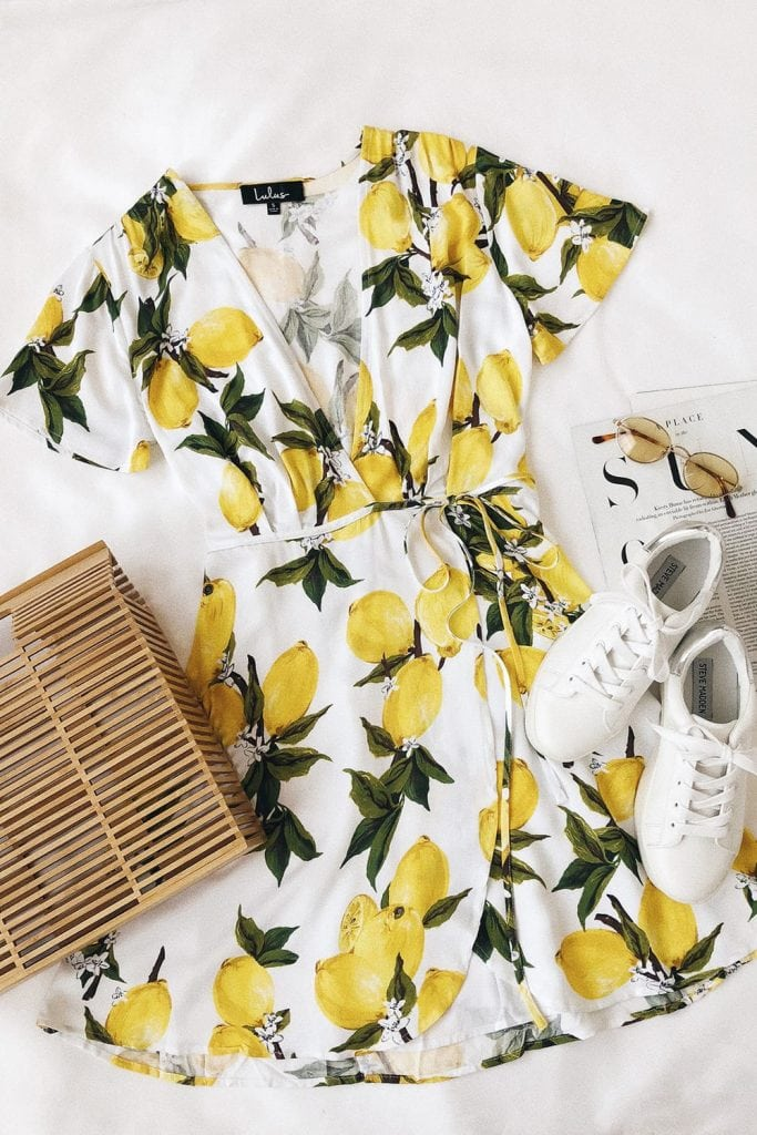 Flat lay featuring short-sleeved lemon print wrap dress, wooden bag, small oval sunglasses, and white sneakers, with part of an open magazine visible in the background