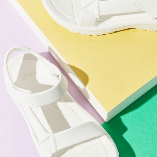 White rubber Teva sandals against a green and pastel yellow and lilac-colored background.