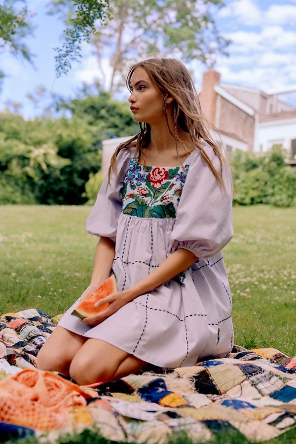 Woman wearing embroidered puff sleeve dress sitting outside on blanket and holding watermelon slice