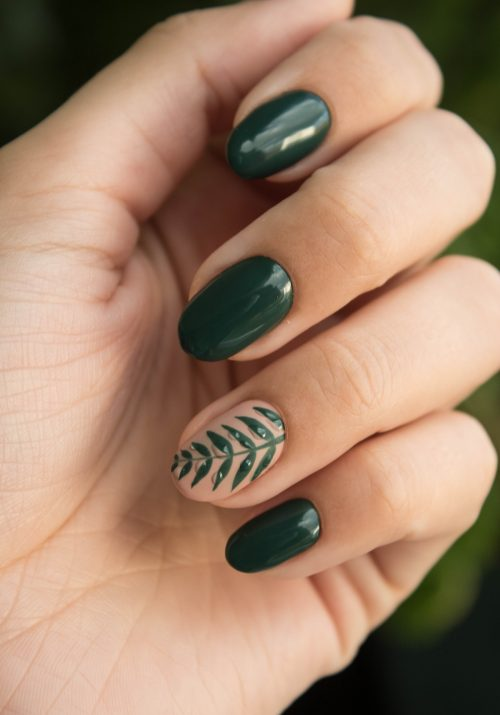 Close-up shot of dark green painted nails with leaf accent nail on ring finger