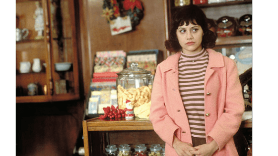 Daisy from Girl Interrupted in a pink jacket and striped top