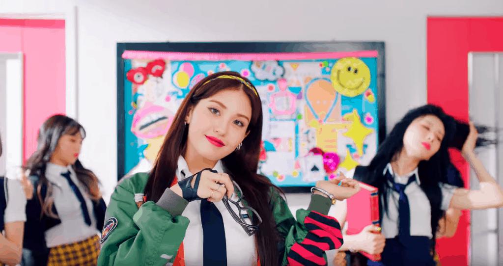 Jeon Somi in her Birthday music video wearing green jacket, black tie, white oxford shirt