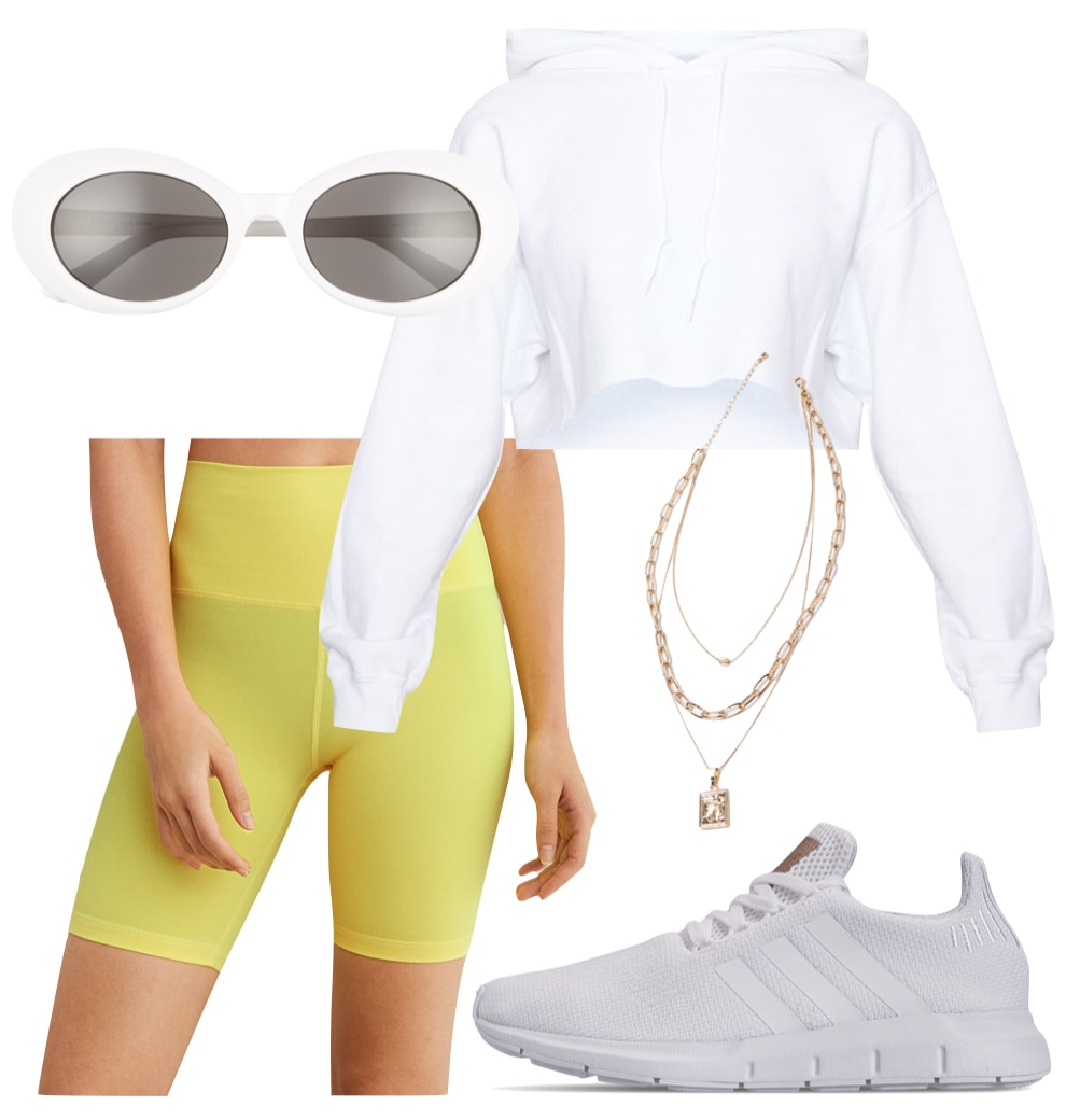 Gigi Hadid Outfit: white cropped hoodie, neon yellow biker shorts, white oval sunglasses, layered gold chain necklaces, and white sneakers