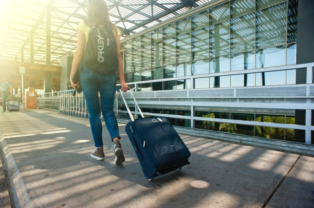 Ways to travel cheap - join a frequent flyer program. Traveler pulling a suitcase through airport.