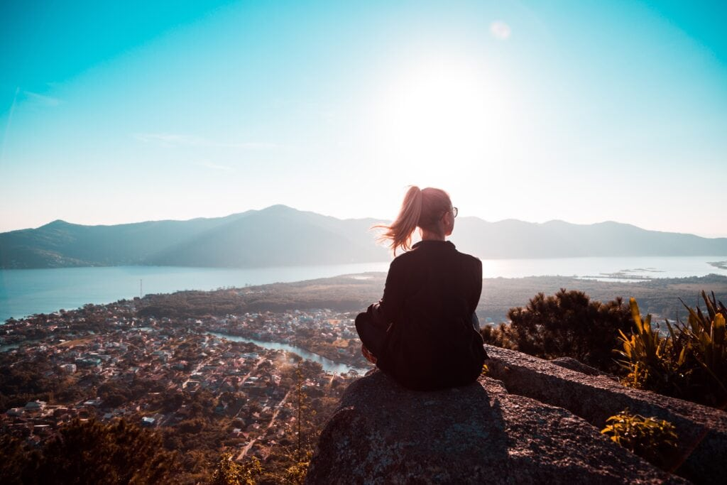 Tips for introverts in college - Woman sitting alone in nature, looking at the mountains.