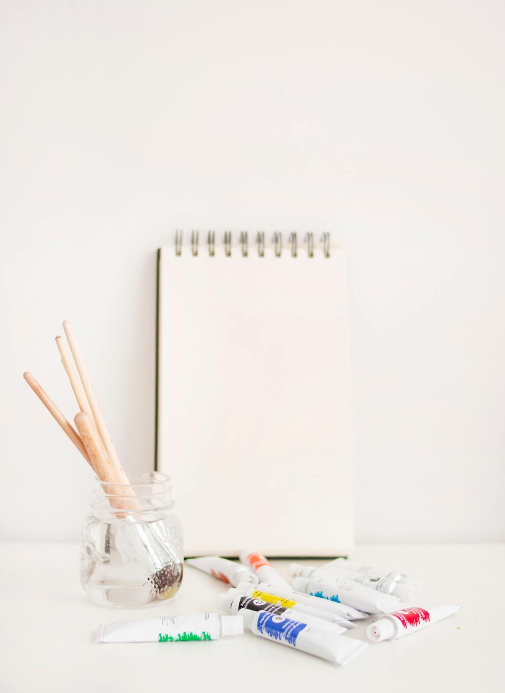 Paintbrushes, paint, and an empty notebook